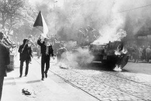 Czechoslovaks carry their national flag past a burning Soviet tank in Prague.